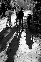 Family stop to chat on their way cycling through a forest, Provence, France.