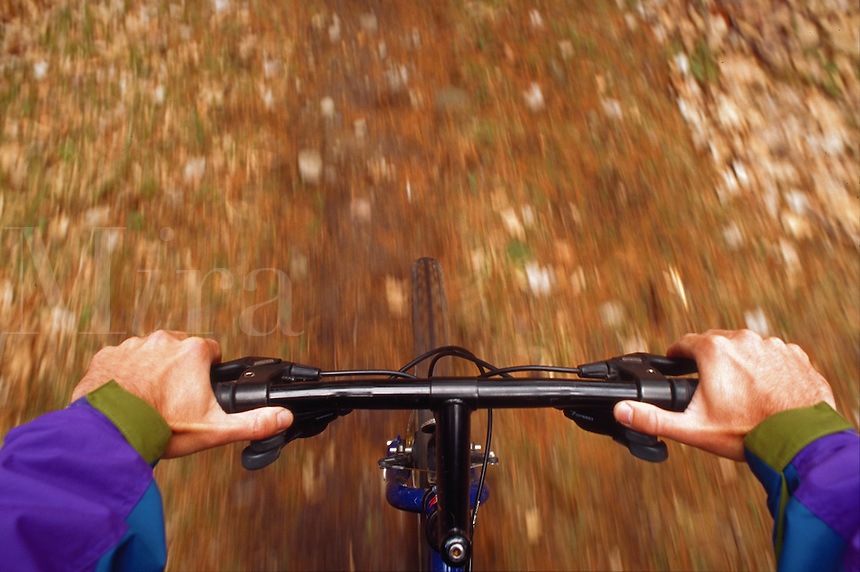 View of mountain biker's handlebars along the trail