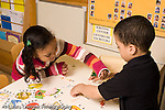 Preschool Headstart 3-5 year olds puzzle literacy boy and girl working on puzzles showing object and word horizontal