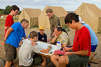 Photo story of Philmont Scout Ranch in Cimarron, New Mexico, taken during a Boy Scout Troop backpack trip in the summer of 2013. Photo is part of a comprehensive picture package which shows in-depth photography of a BSA Ventures crew on a trek. In this photo, newly arrived Boy Scouts  and advisors review their Philmont map as they begin to put a plan together for their next departure from base camp into the backcountry.<br /> <br /> Photo by travel photograph: PatrickschneiderPhoto.com
