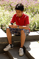 Montreal (Qc) CANADA - August 19 2009 - model released photo - asian (Filipino) male teen texting in front of Notre-Dame Basilica in Old-Montreal.