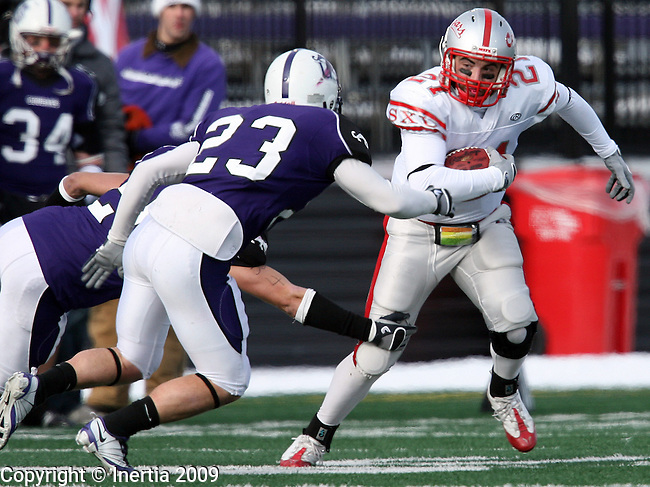 SIOUX FALLS, SD - DECEMBER 5:  Joe Coia #21 of the University of St. Xavier tries to escape the defense of Trevor Holleman #28 and Cody Cavender #23 of the University of Sioux Falls in the first quarter of their NAIA semifinal game Saturday afternoon at the USF Complex in Sioux Falls. (Photo by Dave Eggen/Inertia)