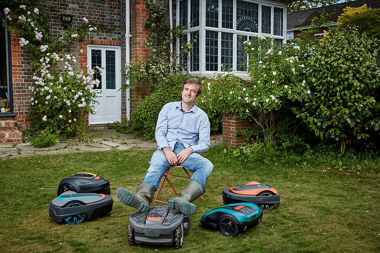 Photograph by John Angerson. 200522. <br /> Times Science Editor Tom Whipple in his garden in Reading Berkshire, with the range of robotic lawn mowers he has been testing.