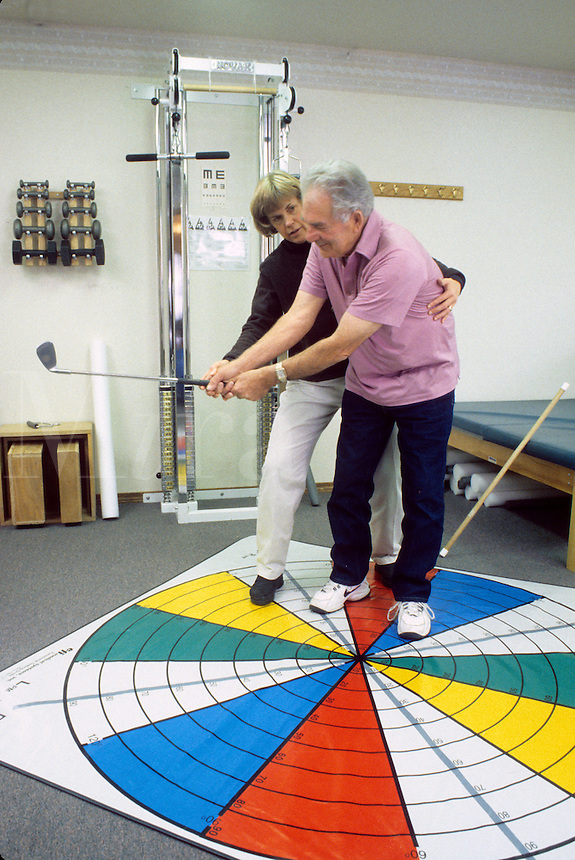 Released, physical therapist assists senior man on lower extremity grid