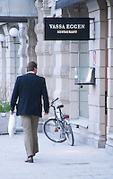 The entrance to the high class gastronomic restaurant Vassa Eggen (the sharp edge) with a bicycle parked outside a man wearing a black jacket walking past and looking at the restaurant Stockholm, Sweden, Sverige, Europe