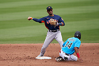 Houston Astros second baseman Robel García (9) throws to first base as Magneuris Sierra (34) slides in during a Major League Spring Training game against the Miami Marlins on March 21, 2021 at Roger Dean Stadium in Jupiter, Florida.  (Mike Janes/Four Seam Images)