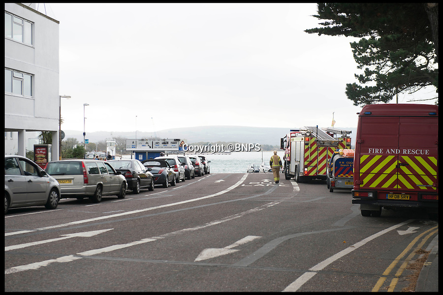 BNPS.co.uk (01202 558833)<br /> Pic: LauraDale/BNPS<br /> <br /> Traffic and emergency services of the ferry slipway.<br /> <br /> An elderly woman has today been rescued from her sunken car after she 'deliberately' drove into a harbour in front of stunned day-trippers.The motorist, aged in her 70s, wound down both windows of her Volkswagen Golf before speeding down a ferry slipway and into the water.As the silver car was swept 100 yards out to sea by the fast tide the woman sat motionless in the flooded driver's seat, ignoring cries from witnesses on the quayside to get out.A brave crew member of a passing fishing boat then dived into the water and pulled the woman free just moments before her vehicle completely sank.