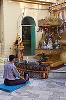 Myanmar, Burma, Yangon.  Sule Pagoda.  Early-Morning Worshiper Praying in front of Buddha Shrine.