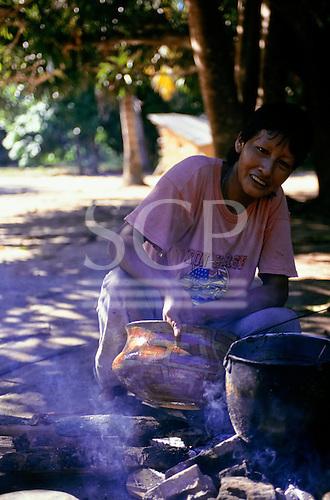 Koatinemo village, Brazil. Assurini Indian woman, Mira, applying vegetable glaze (resin from the Jatoba tree) over a fire.