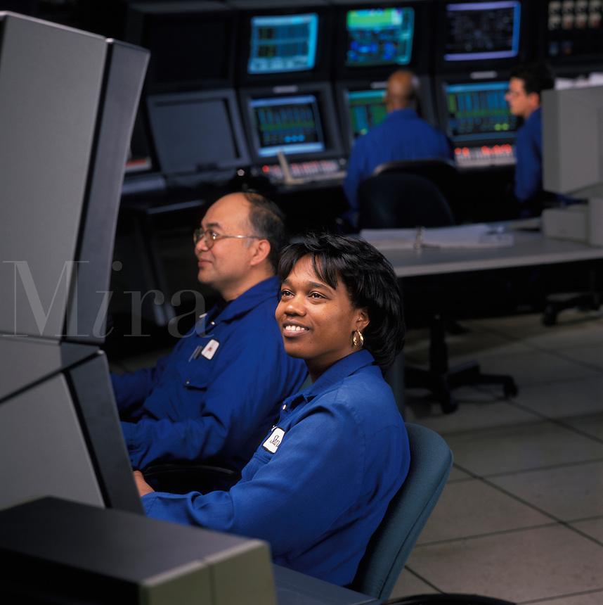 technicians in oil refinery control room