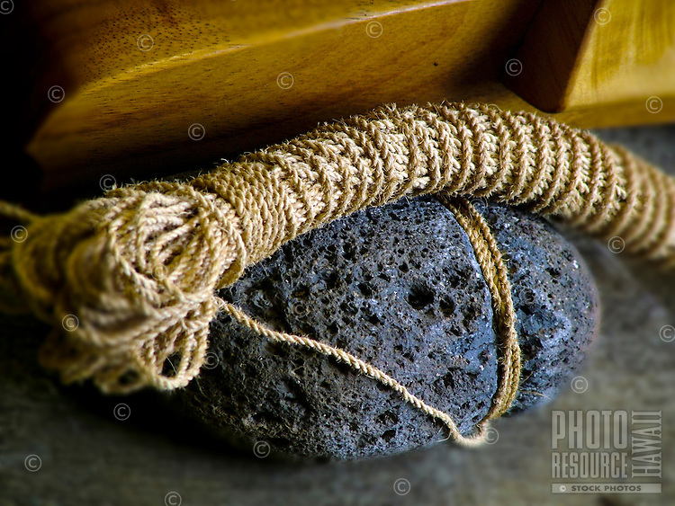 An aa lava rock and rope used as an ancient Hawaiian canoe anchor. On display at Bernice Pauahi Bishop Museum, Oahu.