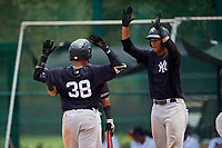GCL Yankees West left fielder Stanley Rosario (38) is congratulated by Anthony Garcia (37) and his teammates as he crosses home plate after hitting a home run in the bottom of the third inning during the second game of a doubleheader against the GCL Braves on July 30, 2018 at Champion Stadium in Kissimmee, Florida.  GCL Braves defeated GCL Yankees West 5-4.  (Mike Janes/Four Seam Images)