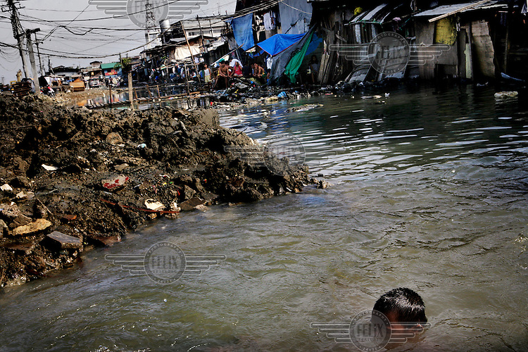 A boy swims in the shanty town of Santo Nino. People in this area live in small homemade huts, many made entirely from rubbish and leftover building materials that they found on the nearby garbage dump. These houses are all illegal, since no one has the acquired permissions to live on the land. People have been living here for up to twenty years - but everyday they might get moved and their neighbourhood demolished to make room for new apartment blocks that they could never afford to buy.