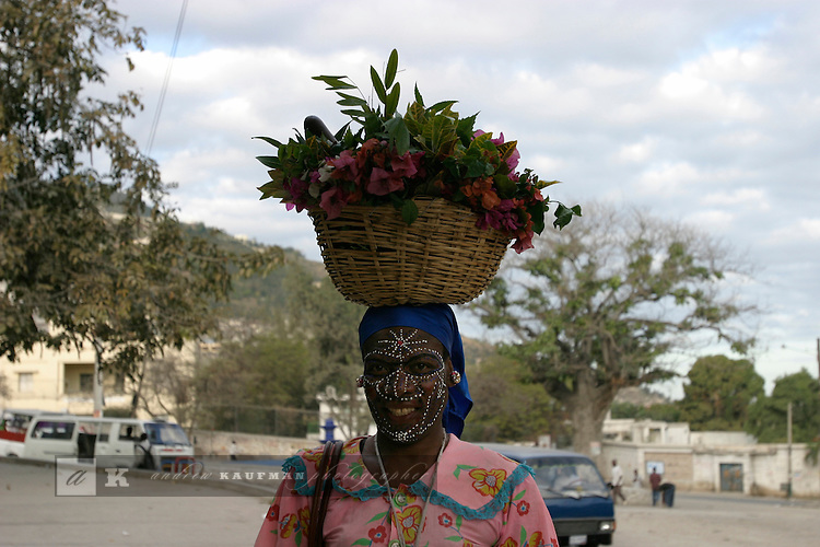 A man dressed as a woman with face paint goes on errands in Petionville.