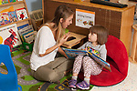 Education Preschool 3-4 year olds female therapist or SEIT working with girl in classroom looking at picture book together