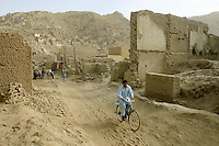 A man rides his bicycle through a part of Kabul totally ruined by many years of war. Kabul,Afghanistan,Asia.