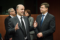 Pierre Moscovici , EU commissioner for Economic and financial affairs, taxation and customs union (L) talks with Valdis Dombrovskis , Vice-president of the European Commission for the euro and social dialogue  at the start of a Eurogroup with European Finance Ministers meeting at EU council headquarters in Brussels, Belgium on 26.01.2015 The Eurogroup's meeting focus on Greece, after  leftist anti-bailout party SYRIZA won parliamentary elections by Wiktor Dabkowski