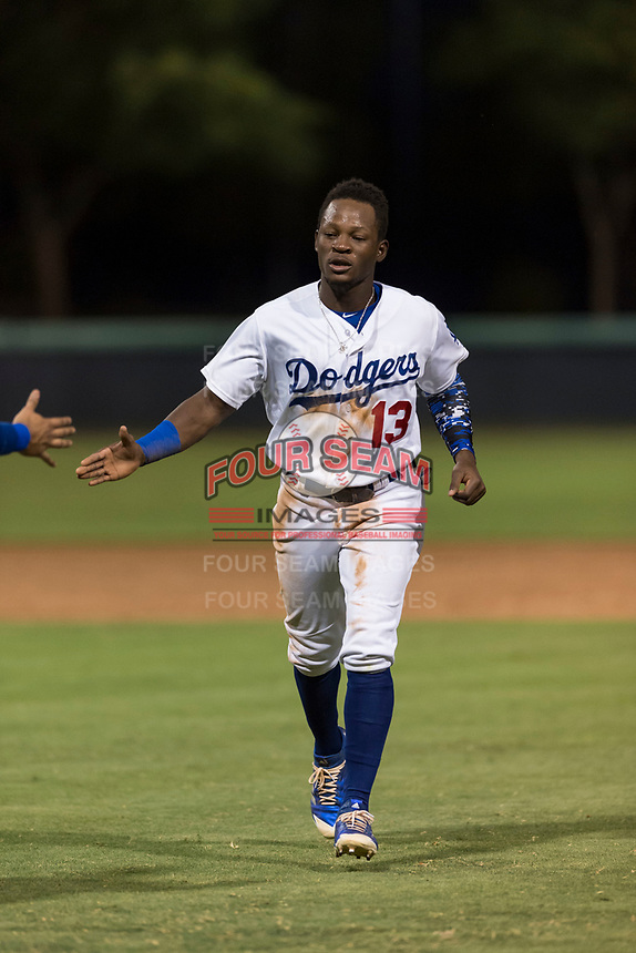 AZL Dodgers center fielder Rolando Lebron (13) is congratulated by a teammate as he runs off the field during an Arizona League game against the AZL Angels at Camelback Ranch on July 8, 2018 in Glendale, Arizona. The AZL Dodgers defeated the AZL Angels by a score of 5-3. (Zachary Lucy/Four Seam Images)