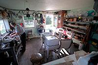 4415 / Waschmaschinen: AMERIKA, VEREINIGTE STAATEN VON AMERIKA,PENNSYLVANIA,  (AMERICA, UNITED STATES OF AMERICA), 14.09.2006: Blick durch das Fenster von Samuel Stolzfus Werkstadt fuer Wassmaschinen, die Amish duerfen aus Glaubensgruenden keinen Strom verwenden. Er ruestet die ueber 30 Jahre alten Geraete mit einem Verbrennungmotor zum Antrieb aus. Samuel Stolzfus war Farmer ist jetzt aber zu alt und verdient etwas Geld mit dieser Arbeit.