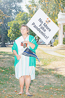 "A woman holds a sign reading ""No More Fake Pandemics"" as alt-right organization Super Happy Fun America prepares to demonstrate against facemasks, vaccines, and pandemic closures, and in support of the reelection of President Donald J. Trump near the residence of Massachusetts governor Charlie Baker in Swampscott, Massachusetts, on Sat., Sept. 26, 2020. Super Happy Fun America is most well known for organizing the Straight Pride Parade in Boston on August 31, 2019."