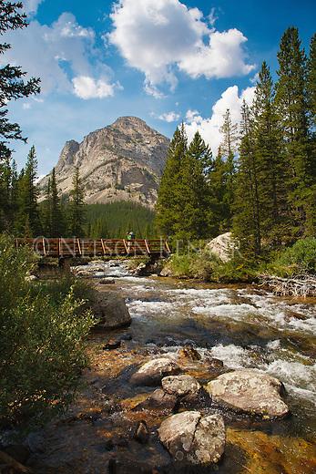 a backpacker walks across the pack bridge crossing the lake fork of rock creek in the beartooth wilderness area in montana