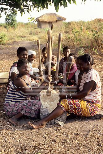 Lake Chaya, Zambia. Young women sitting round a trough pounding yams with pestle sticks.