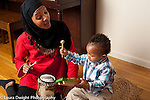 Toddler baby boy playing musical instruments with mother, hitting xylophone with mallet while she hits drum
