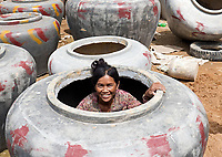 A Cambodian or Khmer women having a last check in one of those huge Urns/Jars that are made for holding water in the Province, Battambang, Cambodia.