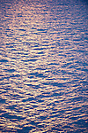 Anilao, Philippines; ripples in the water's surface reflect purple and blue from the sunset colors on the clouds overhead