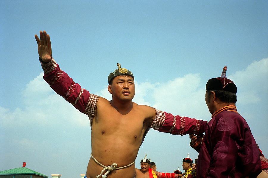"""Zuunmod, Mongolia, July 2003..Competitors and spectators at the Mongolian Wrestling contests in the Llama Naadam. A wrestler """"flies like a falcon"""" around a judge."""