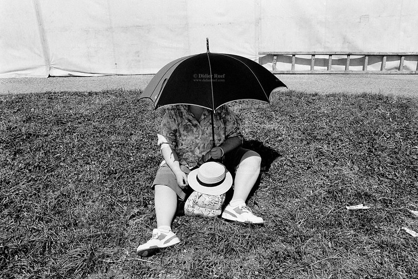 """Switzerland. Canton Jura. Saignelégier. A woman, seated on the grass, protects herself from the sun by covering her face and chest with an umbrella during the traditional """"Marché-Concours"""", which is one of the main Swiss horse events. The horse competition market in Saignelégier is held annually, on the 2nd weekend of August. Saignelégier is also the seat of the district of Franches-Montagnes. © 1991 Didier Ruef"""