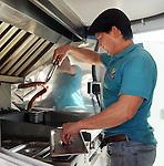 Mario Morales prepares a Texan dog at his Yummy Dog food truck on Durham Thursday Oct 09, 2014.(Dave Rossman photo)