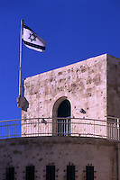 The top section of the old Jerusalem (Israel) city hall, flying an Israeli flag, and clearly showing the bullet holes inflicted by the Jordanian troops in the six-day war (1967).