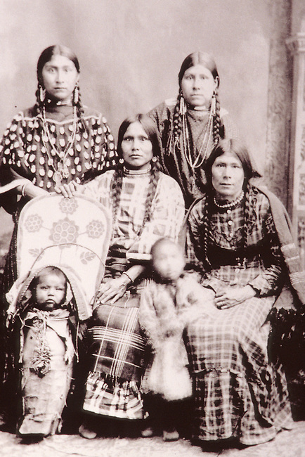 Historic black and white sepia toned Native American family of women dressed in traditional regalia with a young child and baby in papoose cradleboard.