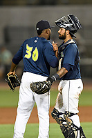 Pitcher Adonis Uceta (30) of the Columbia Fireflies is congratulated by catcher Ali Sanchez (20) in a game against the Charleston RiverDogs on Friday, June 9, 2017, at Spirit Communications Park in Columbia, South Carolina. Columbia won, 3-1. (Tom Priddy/Four Seam Images)