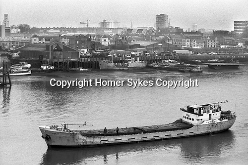 London Docklands Development view across the River Thames to Wapping east London 1980s UK. St George in the East church (top left of image) Cargo boat 1987 England.