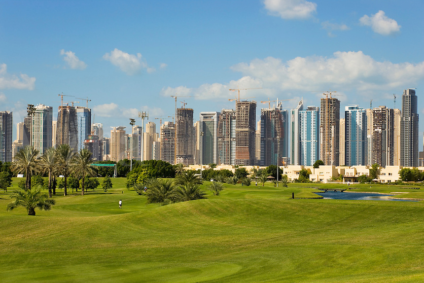 Dubai.  Skyline of Emirates Lakes Towers and Jumeirah Beach Residences overlooks the Montgomerie Golf Course at Emirates Hills.  Villa developments..