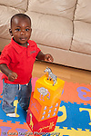 12 month old baby boy standing looking at camera stack of blocks with zebra animal toy on top in front of him vertical