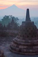 Borobudur, Java, Indonesia.  Stupa and Mount Merapi at Sunrise in Morning Mist.
