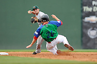 Shortstop Jeremy Sy (2) of the Augusta GreenJackets turns a double play putting out Danny Bethea of the Greenville Drive in a game on Sunday, April 12, 2015, at Fluor Field at the West End in Greenville, South Carolina. Augusta won, 2-1. (Tom Priddy/Four Seam Images)
