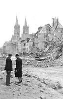 A pair of residents watch a Canadian bulldozer clearing away the ruins of destroyed houses, rue de Bayeux, Caen. In the background, the two towers of the Abbaye aux Hommes remain intact, July 10, 1944