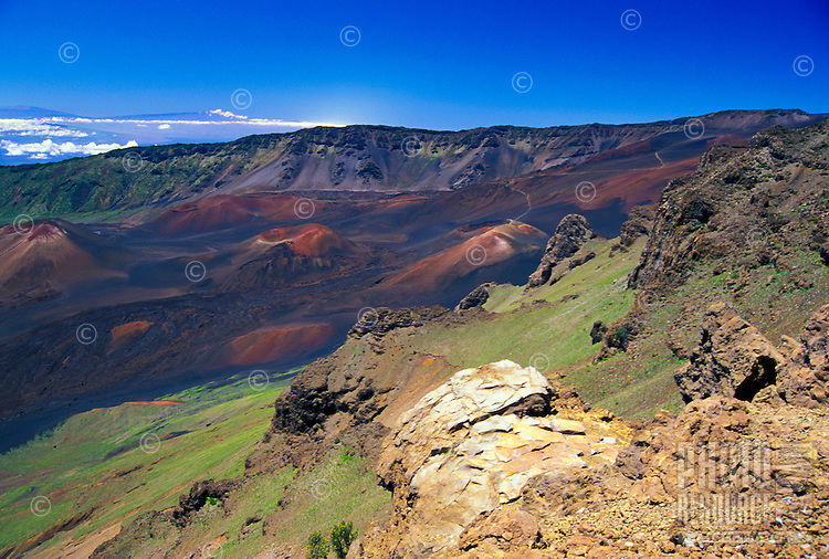 """The Haleakala National Park and """"crater"""" with the summits of the Big Island's Mauna Kea and Mauna Loa 80 miles in the distance. Cinder cones denoting old lava flows and eruptions are below."""