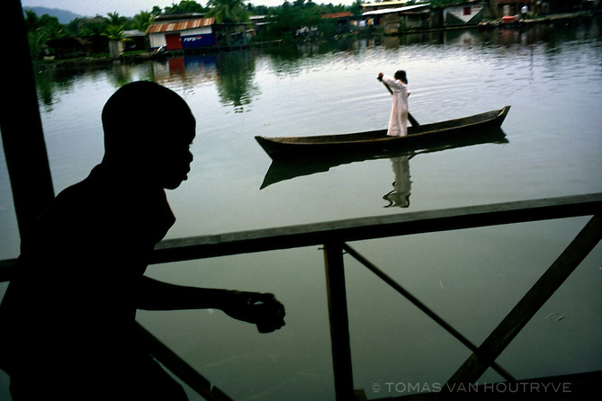 A girl paddles and dugout canoe near the boat docks in Bocas del Toro, Panama in 1999.