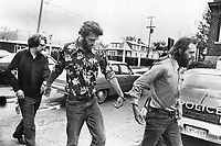 1977 File -<br /> <br /> Handcuffed murder suspects in slaying of 12-year-old shoeshine boy Emanuel Jaques are led to Sioux Lookout police car after being arrested aboard a Canadian National Railways train bound for Vancouver. From left: Joseph Wood; 26; Albert Wayne Kribs; 41; and Werner Greuner; 28. A Fourth suspect; Saul David Betesh; 27; was arrested in Toronto. Boy's body was found in a plastic garbage bag on the roof of a Yonge St. body-rub shop. He had been drowned.<br /> <br /> Photo : Boris Spremo - Toronto Star archives - AQP