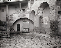 """""""Hidden Cistern in San Gimignano""""<br /> San Gimignano, Italy<br /> 2015<br /> <br /> A secluded cistern stands nobly beneath a stairway adorned with medieval frescoes.  Built in 1361, the cistern bears the coat of arm of the ruling Alberti family.  The cistern provided water for those who lived near the Town Hall, which was built in 1320.  Today, the courtyard steps lead to the Civic Museum of San Gimignano.<br /> <br /> 4 x 5 Large Format Film"""