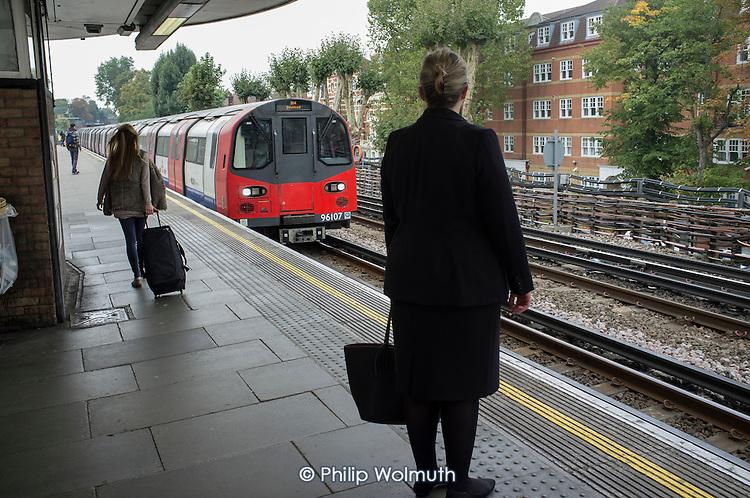 Passengers waiting on KIlburn underground station platform London