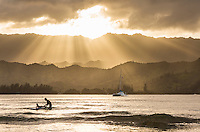 At sunset, a young father teaches his son to surf at Hanalei Bay, Kaua'i.