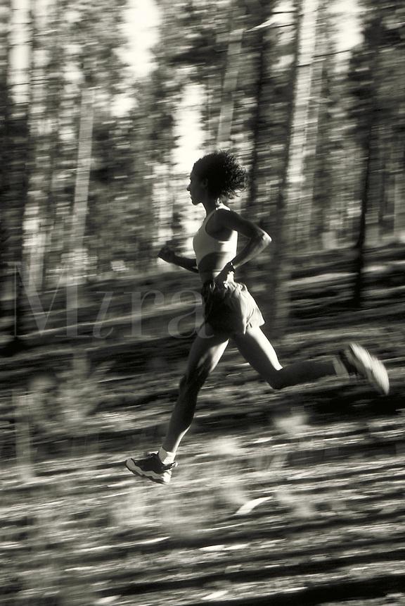 African-American woman running in Colorado forest. Melissa Terhorst MR 615. Colorado.
