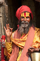 Pashupatinath, Nepal.  Sadhu, a Hindu Ascetic or Holy Man, Offering the Gyan Mudra or Vitarka Mudra Gesture.  This gesture--thumb and index finger touch lightly at tips, other fingers extended upright--ensures mental peace, spiritual feelings, and sharp memory.  The stylized trident on his forehead marks him as a devotee of Shiva.