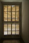Pattern from light through wooden window shutters doorway.
